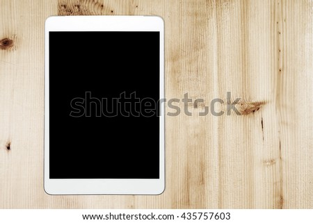 Tablet Computer On Wood Background.