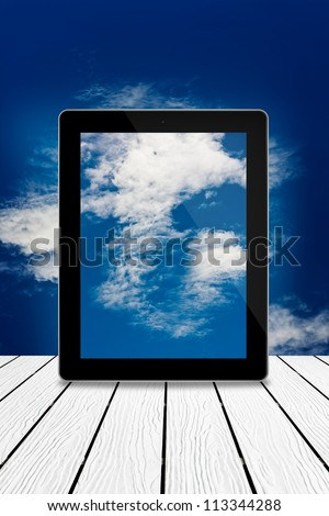 Tablet computer on wood,cloudy sky computing technology concept - stock photo