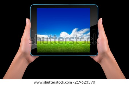 Tablet computer with blue sky and green grass on the screen