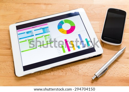 Tablet computer with financial charts on working desk - stock photo