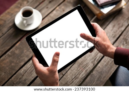 Tablet computer with isolated screen in male hands over cafe background - table, cup of coffee...