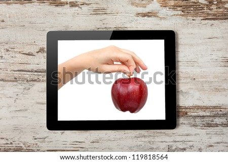 Tablet computer with the hand and a red apple on the screen on a background of wood - stock photo