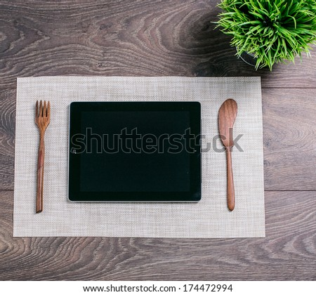 Tablet computer with wooden cutlery and a plant - stock photo
