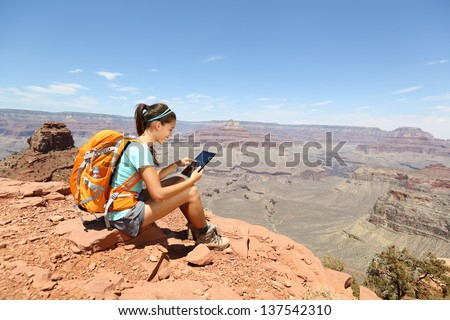 Tablet computer woman hiking in Grand Canyon using travel app or map during her hike. Multiethnic hiker girl relaxing on South Kaibab Trail, south rim of Grand Canyon, Arizona, USA. - stock photo