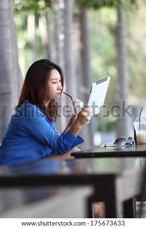 Tablet computer. Woman young smiling mixed race reading relaxed on  tablet