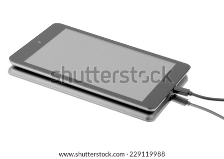 Tablet connected to the cable. - stock photo