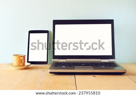 tablet device and laptop with blank screen ready for mock up over wooden table  - stock photo