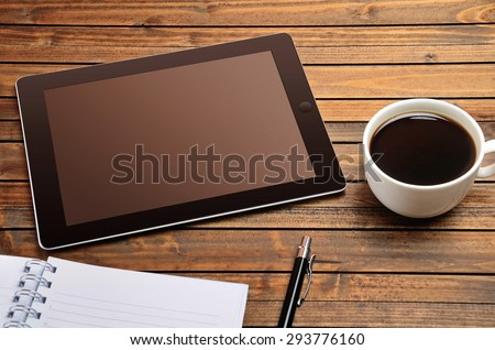 Tablet empty screen with coffee cup on desk
