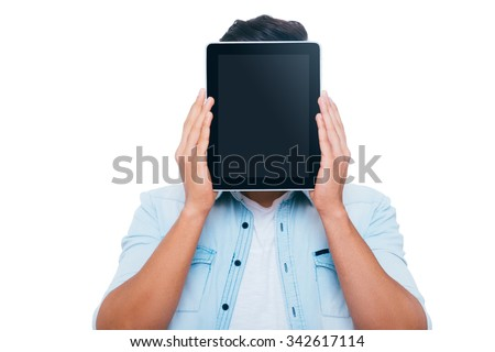 Tablet face. Young man hiding his face behind digital tablet while standing against white background - stock photo
