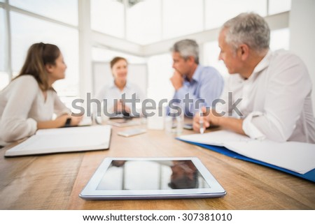Tablet in front of talking business people in the office - stock photo