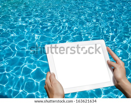 Tablet in hand by the pool - stock photo