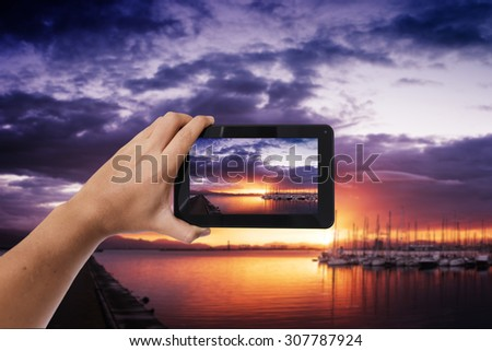 Tablet in hand photo shooting sunset on a harbor - these are all photos made by me, that you separately can find on my shutterstock portfolio. - stock photo