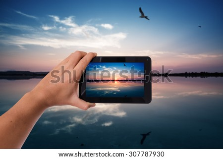 Tablet in hand photo shooting sunset reflection on calm pond - these are all photos made by me, that you separately can find on my shutterstock portfolio. - stock photo