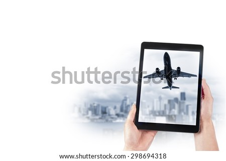 tablet in the hands and the plane over the city - stock photo