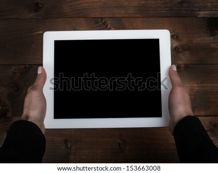 tablet in the hands of the old table