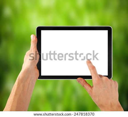 tablet ipades computer in hand on the winter forest backgrounds.  - stock photo