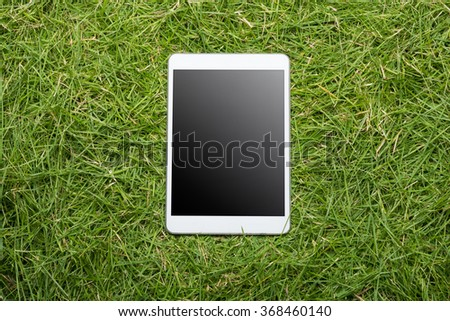Tablet lying on the green grass texture background - stock photo