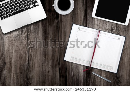 Tablet, notepad, computer and coffee cup on office wooden table - stock photo