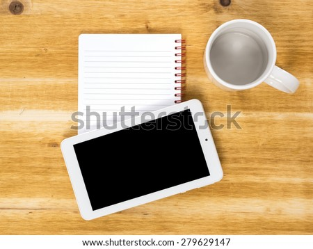 Tablet, notes and cup on work top