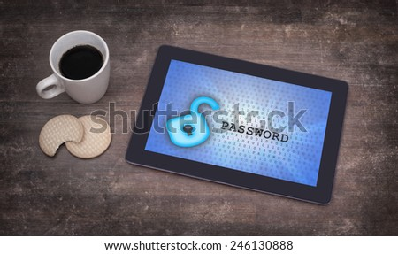 Tablet on a desk, concept of data protection, blue - stock photo