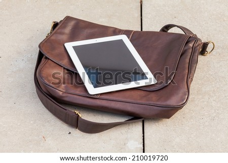 Tablet on a fashionable  bag. Copy space. Outdoor photo. Concept photo. - stock photo