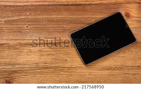 Tablet  on old wooden desk.  - stock photo