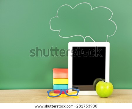 Tablet on table, on green blackboard background - stock photo