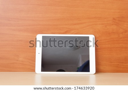Tablet on the table with blank screen - stock photo