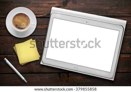 Tablet on wooden planks with coffee