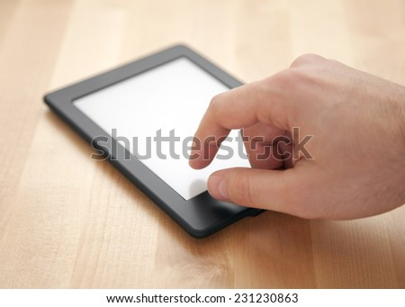 Tablet or e-book reader on wood background