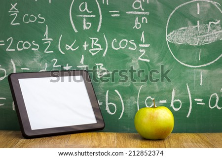 Tablet pc and apple over green  blackboard - stock photo