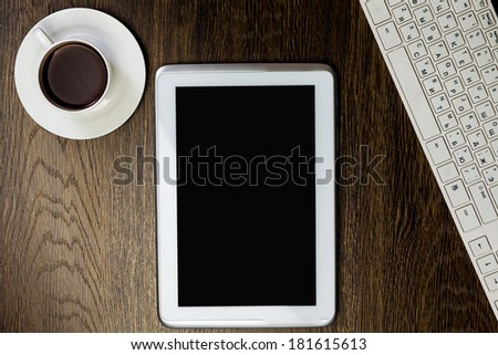 Tablet pc cup of coffee and keyboard at table