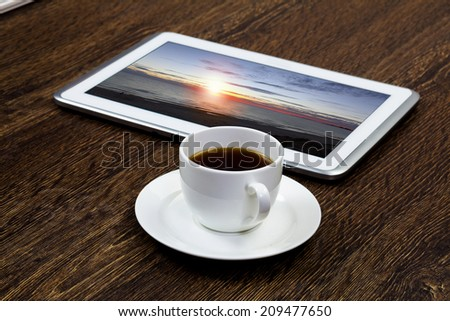 Tablet pc cup of coffee on wooden table - stock photo