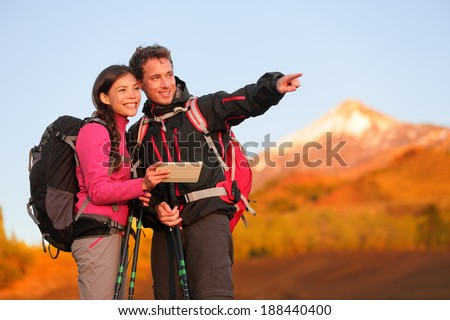 Tablet PC - hiking couple using travel app or map on hike. Man and woman hikers looking at view pointing and showing during hike on volcano Teide, Tenerife, Canary Islands, Spain. - stock photo