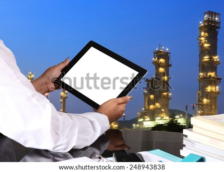 tablet pc in hand  on office table with oil refinery background  - stock photo