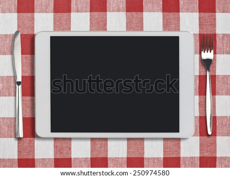 tablet pc looking like ipad, fork and knife on red checked tablecloth - stock photo