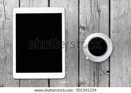 Tablet pc looking like ipad on table with coffee cup - stock photo