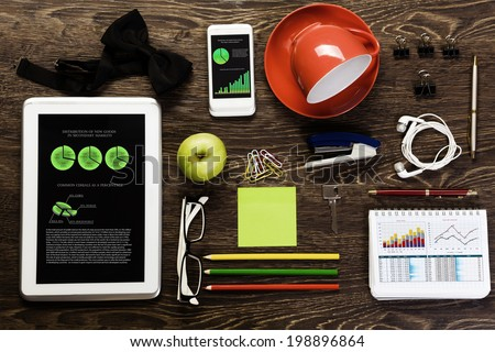 Tablet pc mobile phone and stationary items on wooden table - stock photo
