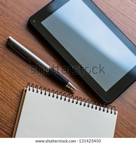 Tablet PC, notebook and pen a book on an office desk - stock photo