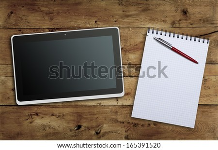 Tablet PC notebook and pen on the table of the old oak wooden planks closeup - stock photo