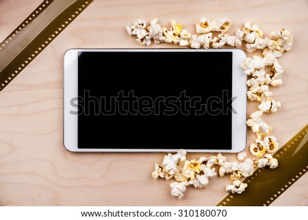 Tablet pc on dark background with attributes of cinema. Visual metaphor for content consumption - films and media on a mobile device. - stock photo
