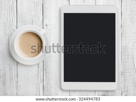 Tablet pc on white table desk with coffee cup