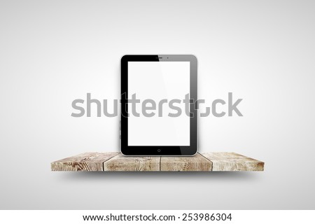 Tablet pc same with ipade on wooden shelf over white background - stock photo