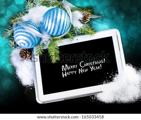 Tablet PC with Christmas decoration on black - stock photo