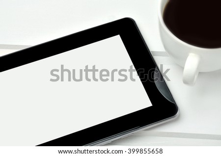 Tablet pc with cup of coffee on white wooden table - stock photo