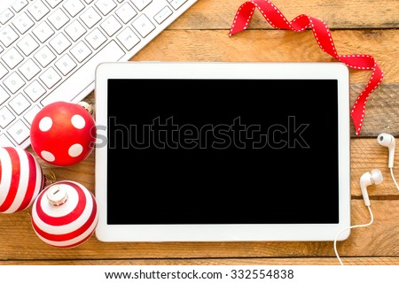 Tablet pc with headphones, keyboard and christmas balls on wooden background