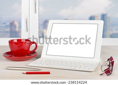 Tablet PC with keyboard and red mug on office table - stock photo
