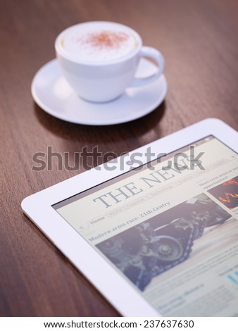 Tablet PC with launched news site or application on it and cup of coffee