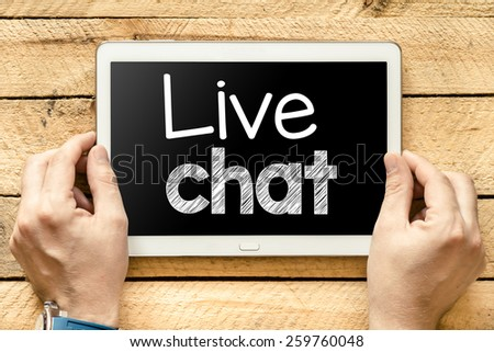 Tablet pc with live chat. Male hands holding tablet pc with live chat on wooden background - stock photo