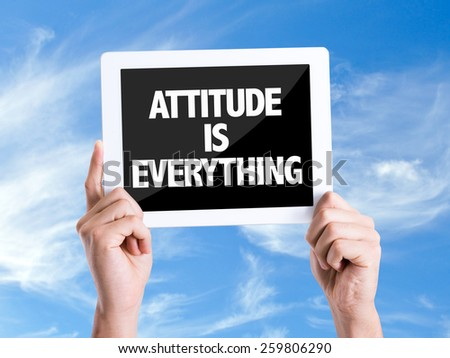 Tablet pc with text Attitude is Everything with sky background  - stock photo